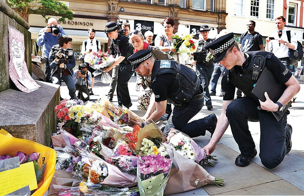 Police offices add to the flowers for the victims of Monday night pop concert explosion, in St Ann's Square, Manchester, Tuesday May 23, 2017.